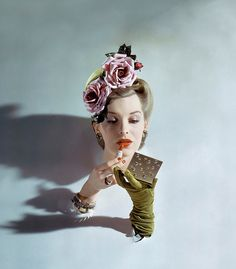 A model applies lipstick in a most unconventional manner in this John Rawlings photograph, which appeared in the March 15, 1943, Vogue. Her head and forearms are protruding from what appears to be a wall, and she is impeccably attired in bracelets, gloves, and even a flower-studded hat. This piece is quite surreal, and it's a rare example of a high-concept, offbeat photograph from the era.
