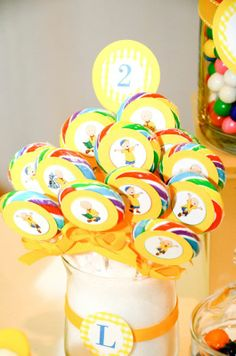 very intricate caillou birthday party! cute idea to add paper circles touches to these colorful lollipops!