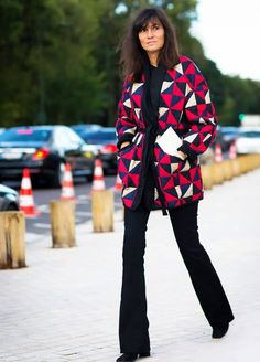 Emanuelle Alt wears a bright checkered blazer and black top with black jeans and boots.