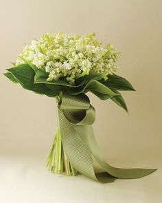 Lilies of the valley are wrapped in a pale-green patterned ribbon for a simple but still luxurious bouquet.