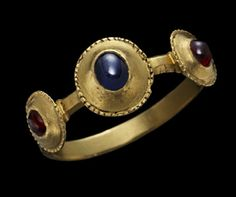 "Gold ring, the hoop terminating at shoulders supporting the triple ""pie-dish"" bezel set with a sapphire between two garnets, all ""encabochon"". 13th /14th centuries."