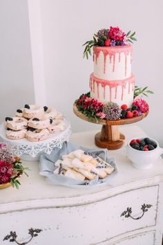 A raspberry glaze brings a splash of color to a white-chocolate cake complemented by rings of berries, greenery, and blush and lavender organic florals.