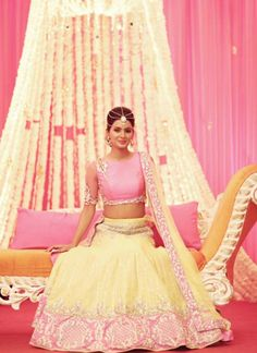 Graced by Bollywood beauty Geeta Basra on her mehendi ceremony, this lime yellow & fuchsia raw silk lehenga choli featuring pita embroidery gives a contemporary vibe and is sure to give you that resplendent look on a special occasion. It comes with a net dupatta with embellished border.