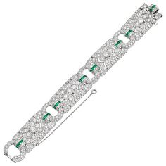 For Sale on 1stdibs - Exceptional Art Deco bracelet, designed with four pierced panel links set with circular-cut diamonds and accented by buff-topped calibre-cut emeralds,
