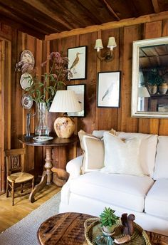 If you want keep the wooden color for a rustic room, but don't want the space to feel too dark or dated, use your accessories wisely: A small gallery wall and a large, show-stopping mirror gladly take the attention away from the deeply stained wood. See more at Carla Aston » - HouseBeautiful.com
