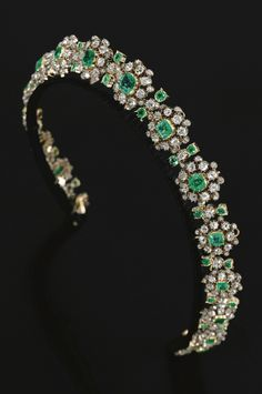 EMERALD AND DIAMOND NECKLACE/ TIARA, MID 19TH CENTURY, Designed as a graduated row of seventeen cluster motifs, each centring on a step-cut emerald within a border of cushion-shaped and circular-cut diamonds, length approximately 400mm, accompanied by a tiara fitting, inner circumference approximately 360mm, fitted case.