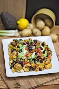 Nacho Potatoes: vegetable broth, bragg liquid aminos, black beans, corn, red pepper, green chiles, liquid smoke, lime, cilantro, cauliflower queso, sour cream, salsa, avocado, green onions, black olives, pickled jalapeños