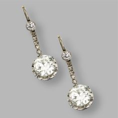 PAIR OF DIAMOND PENDANT-EARRINGS Set with 2 old European-cut diamonds weighing approximately 3.40 carats, within platinum frames, supported by a fringe set with old European-cut and single-cut diamonds, mounted in platinum and white gold.