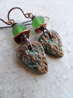 These earrings feature beautiful polymer clay charms, expertly handcrafted by Elsie Smith, and unusual beads lampworked from green sea glass.