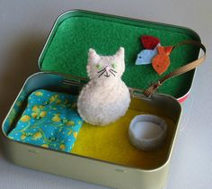 This chubby little cat measures 1 3/4 tall. It was carefully hand stitched and stuffed with polyester fiberfill. Embroidery floss was used for detailing. Included with my Altoid tin playset is a sewn down cotton floral cozy bed with tiny french knots to look like buttons. Theres also a