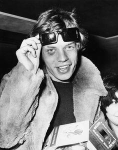 'The Rolling Stones' lead singer Mick Jagger lifting up his sunglasses to reveal a black eye, which he received on tour in France, as he signs autographs for fans at London Airport, April (Photo by Ted West/Central Press/Hulton Archive/Getty Images) Mick Jagger, John Paul Jones, Robert Plant, Jimmy Page, Rock And Roll, Grunge, Idole, Keith Richards, Jim Morrison