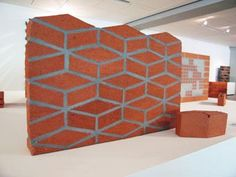 Brick can be used in many different ways than it has been traditionally, and this image showcases just how one may do that. This technique, known as the Cube Brick, alters the normal horizontal lines that bricks create, allowing for a new set of patterns to emerge from traditional material.