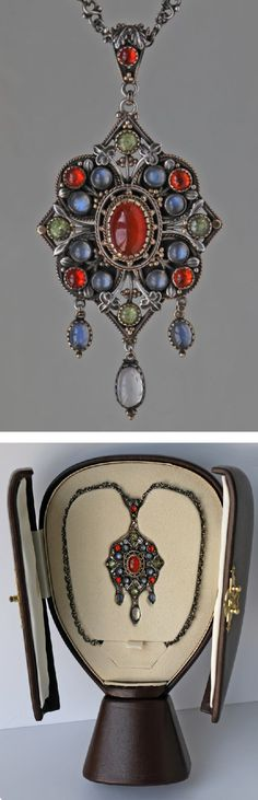 Arts & Crafts jewelled pendant, UK, circa 1900. This gorgeous silver and gold pendant is of Puginesque Gothic form, incorporating a quatrefoil against a diamond shaped frame with cabochon fire opals, moonstones & peridots set with delightful Gothic leafage.