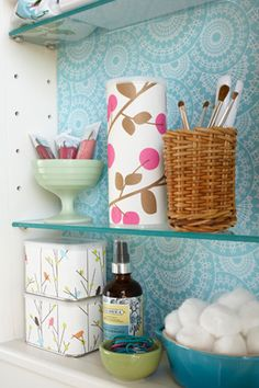 Love the scrapbook paper to brighten up the medicine cabinent AND the super cute mix of containers.