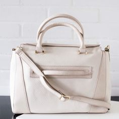 Danielle Nicole Ivory Vegan Leather Satchel Bag Available now. Made of quality faux leather materials for an ultra soft and durable feel. White and cream Colorblocked colors. Top zip closure. Gold hardware. Adjustable Crossbody strap and top handles. Danielle Nicole Bags Satchels