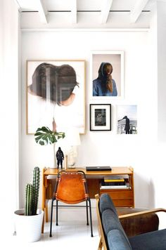 framed modern photos, a cactus, a fig leaf.                      20 Crazy-Cool Workspaces to Inspire Your Most Productive Year Yet | MyDomaine