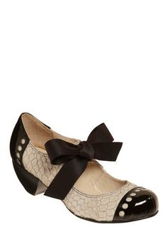 spiced-up Mary Janes, vamp of silver-edged white scales, stacked, wood-like heel, in the shape of a unique, tapered semi-circle. Patent black leather and avant-garde circle cutouts adorn the rounded toe and heel cap, and a flirty satin bow decoration