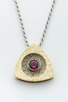 Spyro Triangle Pendant 14K with Rubellite Tourmaline by Marie Scarpa. Spyro Triangle pendant 14K textured yellow gold with 14K white gold hand-woven wire center. Set in the center of the pendant is one bezel set 6mm 1.06ct rubellite tourmaline. The pendant is 1
