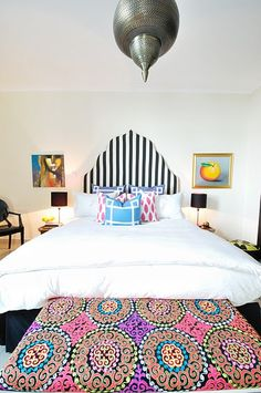 This is almost exactly what I want to do with my bed. I can't decide between a black and white striped headboard slipcover or curtains. And I'm not crazy about that light fixture. But other than that- identical.