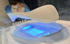 A member of V Museum staff looks over a model of the London 2012 Olympics Aquatics Centre, designed by Zaha Hadid