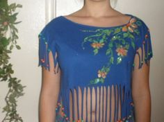 Cropped Painted T shirt with a Modern Hippie look and beaded fringe. Royal Blue T shirt designed with a Peek-a-Boo Stomach in a baseball shirt hem and almost neon color beaded fringe. I created this One-of-a-Kind tee using a 6 step process including the fringed design which is cut shorter at the sides and embellished with beads, gold studs, and quality glitter.  Women Medium size Pre-shrunk Cotton.~