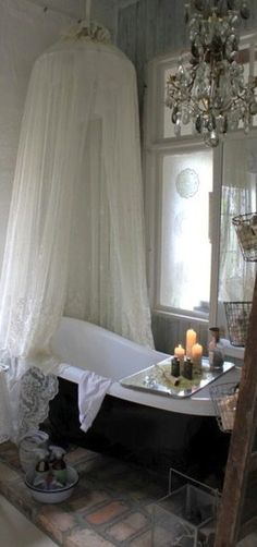 Charming bathroom. Love the canopy over the end of the bath tub. It gives a little feeling of coziness and privacy.