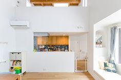 リビングダイニングからキッチンを見る。白の空間に、木とタイルの色が映える。