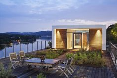 Beautiful waterfront home with deck and outdoor dining. By: Specht Architects