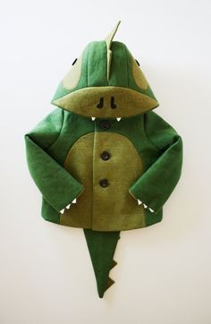 THE CHEEKY GREEN DINOSAUR COAT~  Children's coat features soft felt claws and teeth, a ridged hood, back, and tail, and a quilted tummy panel.   There are 3 black buttons, & 2 side seam pockets as well.   MEDIUM:  soft wool blend felt; interlined with poly fleece/fully lined with poly charmeuse.  DESIGN: LittleGoodAll, on etsy.  PRICE: $165.00