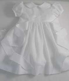 A white Dotted Swiss cotton voile dress and bloomers.  Perfect for a Christening. The slightly high-waisted bodice has horizontal tucks,  a peter-pan collar, self- piped,  and little puff sleeves with bias cuffs. The skirt is very full and it ties at the back with a sash. Shell buttons complete the detail. Bloomers are included to cover the nappy. Fully lined in white cotton lawn …