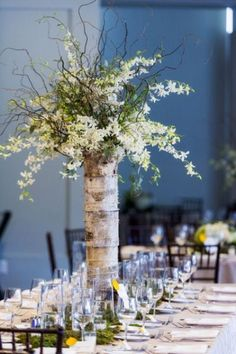 a tall vase wrapped with birch bark and with flowers on branches