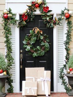 Mallory of Charming in Charlotte decked out her front door with a magnolia leaf wreath and garland. Bright ornaments in red, silver, and gold tones add a pop of color to decor. Mallory's Styling Tip: For a picture-perfect finish, stack kraft paper wrapped gifts against the door./