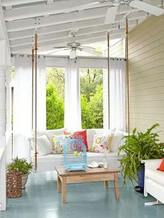 Porch with curtains and a cushioned porch swing. LOVE how cozy this feels!