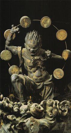 Raijin 雷神 Shinto God of Thunder holding a hammer to beat the drums that surround him. 13th century, wood, Sanjūsangendō in Kyoto. Japan - 風神・雷神像 ともにインド最古の聖典とされる「リグ・ヴェーダ」に登場する神で、その名が示すように自然現象を神格化した原初的な神々です。 風神は、ヴァーユと呼ばれ、数頭立ての馬車で天を駆けて悪神を追い払い、富貴栄達を授ける神とされ、一方の雷神は、ヴァルナという水神だといわれます。 仏教では、仏法を守る役目とともに、悪をこらしめ、善を勧めて風雨を調える神と信じられています。 その像形は、古代の信仰や伝説的空想によって、全く日本化されており、後世の二神のイメージを決定づけた名作で、お堂の再建時に造像を統括した湛慶が、その作成に深くかかわっているとされます。
