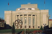 """The Volksbühne (""""People's Theatre"""") is a theater in Berlin, Germany. Located in Berlin's city center Mitte on Rosa-Luxemburg-Platz (Rosa Luxemburg Square) in what was the GDR's capital. The Volksbühne was built during the years 1913 to 1914 and was designed by Oskar Kaufmann, with integrated sculpture by Franz Metzner. It opened on December 30, 1914 and has its origin in an organization known as the """"Freie Volksbühne"""" (""""Free People's Theater"""") which sketched out the vision for a theater """"of…"""