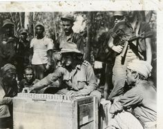 Headmen of mountain villages in Central Burma are reimbursed with silver rupees for livestock killed in recent action by Capt Terence E Carroll, British Civil Affairs Officer. Photographer Unknown