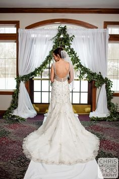 White Chiffon backdrop with greenery accents at WeaverRidge Golf Course.  Perfect for indoor ceremony and bridal backdrop.  Country wedding decoration for winter, spring, summer or fall wedding.  Simple and elegant wedding backdrop.
