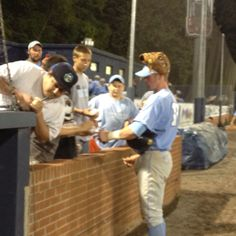 Colin Moran finds a good storage spot for his glove as he signs autographs after 10-4 win over Asheville.