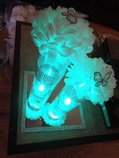 LED Quinceanera Centerpiece Idea, Tall vase, LED lighting, tissue pom poms with butterflies and rhinestone ribbon wrap #quinceaneracenterpiece #quinceanerabutterfly #afloral photo credit: Priscilla Cavazos via pinterest