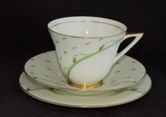Doulton deco: Yvonne tea trio, V1653, c1937-39 (pattern). Abstract green and gold gilt foliate and curvalinear design with gold gilt highlights and trim.