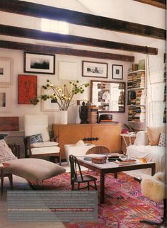 exposed beams, salon wall, stacks of books, traveled vibe, tiny chairs, pink/orange kilim, sheepskin, cozy & lived in, perfect light, #livingroom, #anellegandelman