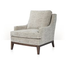 An upholstered chair, the loose pillow back between downswept arms with welt details, the cushion seat above a padded and exposed maple seat-rail and square tapering legs.