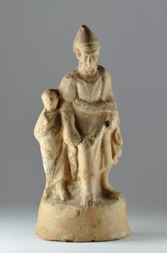 Greek terracotta statuette of elderly man with youth, Hellenistic period, 3rd-2nd century B.C. The man stand barefoot, wearing a robe with sash at his waist and a pointed cap and holds the hand of a youth, wearing a robe and holding an uncertain object over his shoulder, traces of white pigment, large A maker's mark stamped on back of base, 17.8 cm high. Private collection