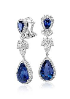 Vibrant color is captured in these exquisite earrings, showcasing 5.29 carats of blue sapphires highlighted by a dazzling halo of pavé-set diamonds.