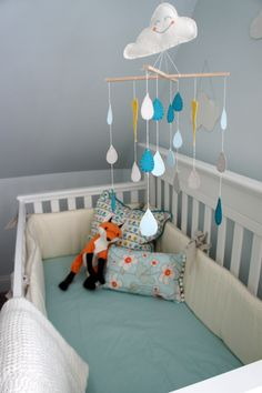 Baby bed in white, blue, and orange for baby girl, with cloud mobile at The Humble Nest.