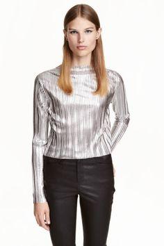 Blusa plissada: Blusa plissada curta em tecido brilhante e macio. Modelo com decote direito, mangas compridas e orlas sem acabamento.