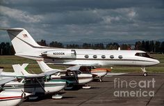 """Mother Hen"" photograph. This Gumman Gulfstream II private jet looks like a mother hen next to a row of smaller Cessna airplanes. The sun broke through the clouds to illuminate the airplanes, leaving me with a dramatic background of Oregon rain clouds. Prints are available. Photo copyright James B. Toy."