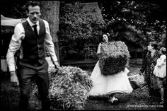 Vicky and Matt moving hay bales before the guests arrive for their Woodland Wedding -