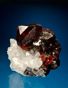 Sphalerite with Quartz - $5000 5.7 x 5.7 cm  NY2-350 - Glowing like a coal in even subtle lighting, this large (3.2 cm), lustrous sphalerite crystal has translucency reminiscent of fine Spanish material. A contrasting bed of quartz prisms adds flash and balance to the piece. The right side of the specimen features crystallized sphalerite as well, though photos don't show them to correct effect here. A high quality sphalerite from this now famous Chinese material.