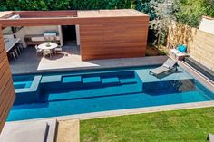 piscine moderne de forme rectangulaire avec marches sous l'eau et abri de jardin…